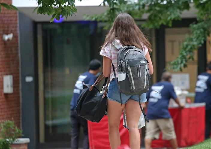 A student walks to her dorm as her belongings are being brought in by professional movers in Medford, MA on Aug. 27, 2020. (Photo by David L. Ryan/The Boston Globe via Getty Images)
