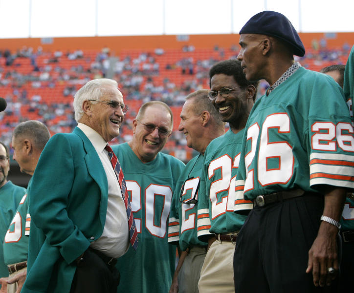 FILE - In this Dec. 16, 2007 file photo former Miami Dolphins coach Don Shula, left, talks with former players from the 1972 undefeated team during a halftime ceremony at a football game against the Baltimore Ravens at Dolphin Stadium in Miami. From left: Shula, Larry Seiple (20), Jim Kiick (21), Mercury Morris (22) and Lloyd Mumphord (26). The perfection of the 1972 Miami Dolphins has earned them the nod as the NFLs greatest team. The 1972 Dolphins edged the 1985 Chicago Bears for the NFLs greatest team in balloting by 59 national media members as part of the NFLs celebration of its 100th season. (AP Photo/Lynne Sladky, file)