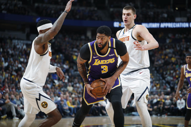 Los Angeles Lakers forward Anthony Davis, center, drives between Denver Nuggets forward Torrey Craig, left, and center Nikola Jokic during the first half of an NBA basketball game Wednesday, Feb. 12, 2020, in Denver. (AP Photo/David Zalubowski)