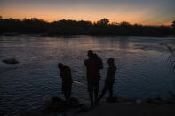 A migrant family stands on the shore of the Rio Grande before crossing from Ciudad Acuña, Mexico, into Del Rio, Texas, at sunrise Sunday, Sept. 19, 2021. (AP Photo/Felix Marquez)