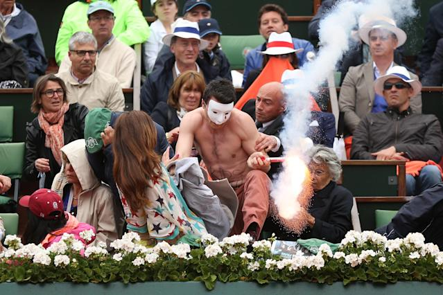 PARIS, FRANCE - JUNE 09: A protester runs onto court with a lit flare before the start of a game in the Men's Singles final match between Rafael Nadal of Spain and David Ferrer of Spain during day fifteen of the French Open at Roland Garros on June 9, 2013 in Paris, France. (Photo by Matthew Stockman/Getty Images)
