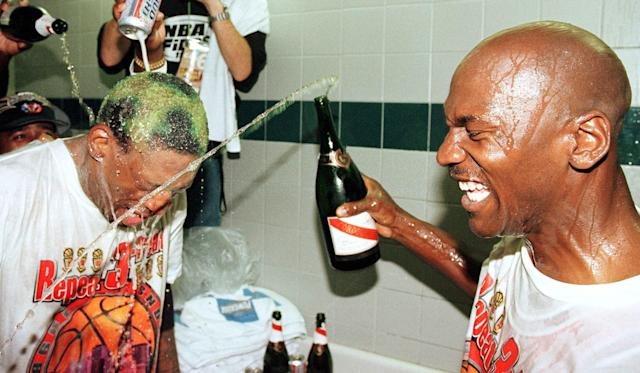 Dennis Rodman gets beer and champagne poured on his head by teammate Michael Jordan after winning the 1997-98 NBA title. That season is the subject of 'The Last Dance,' a 10-part docuseries airing on ESPN. (MIKE NELSON/AFP via Getty Images)