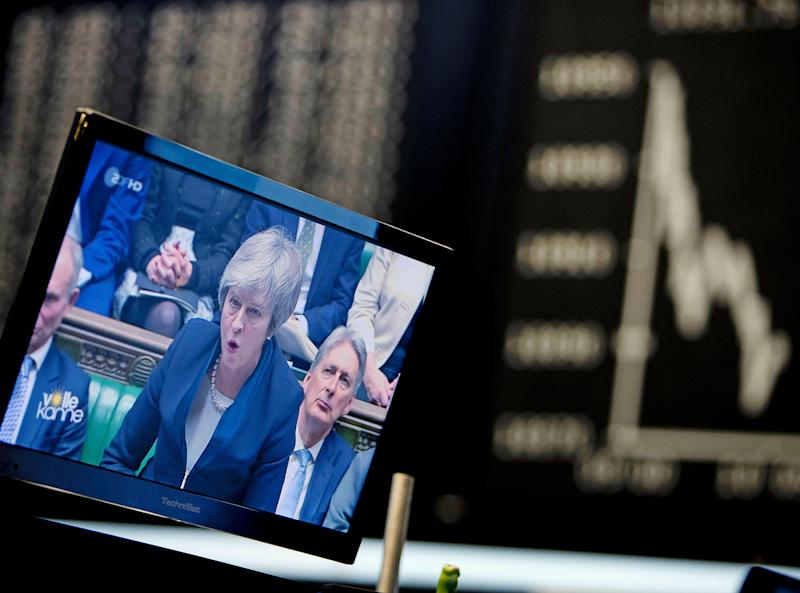 A computer screen shows news about the Brexit with Prime Minister Theresa May as the curve of the German stock index DAX is seen at the stock market in Frankfurt, Germany, Wednesday, Jan. 16, 2019. (AP Photo/Michael Probst)