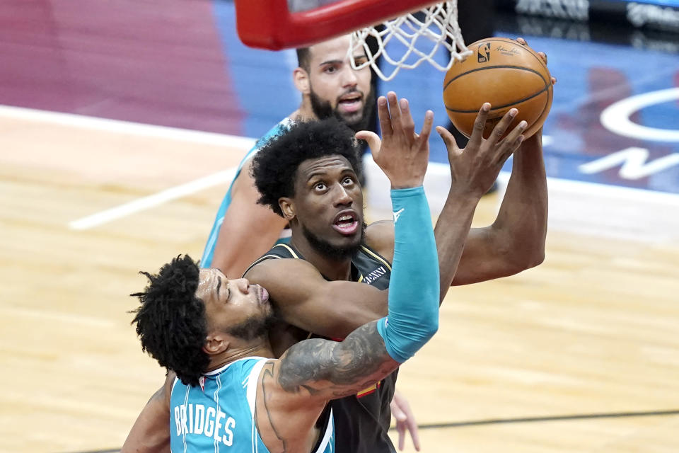Chicago Bulls' Thaddeus Young, center, scores against Charlotte Hornets' Miles Bridges, left, during the first half of an NBA basketball game Thursday, April 22, 2021, in Chicago. (AP Photo/Charles Rex Arbogast)