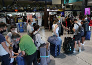 People queue to check-in at the Biarritz airport, southwestern France, Friday Aug.14, 2020. British holidaymakers in France were mulling whether to return home early Friday to avoid having to self-isolate for 14 days following the U.K. government's decision to reimpose quarantine restrictions on France amid a recent pick-up in coronavirus infections. (AP Photo/Bob Edme)