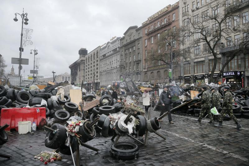 People pass by barricades near the Dnipro Hotel in Kiev, Ukraine, Tuesday, April 1, 2014. A tense standoff between Ukrainian police and a radical nationalist group Right Sector ended Tuesday, when its members surrendered their weapons and left a downtown hotel. Their departure followed a shooting spree in the capital, in which a Right Sector member shot and wounded three people outside a restaurant adjacent to the capital's main Independence Square, including a deputy mayor of the capital. (AP Photo/Efrem Lukatsky)
