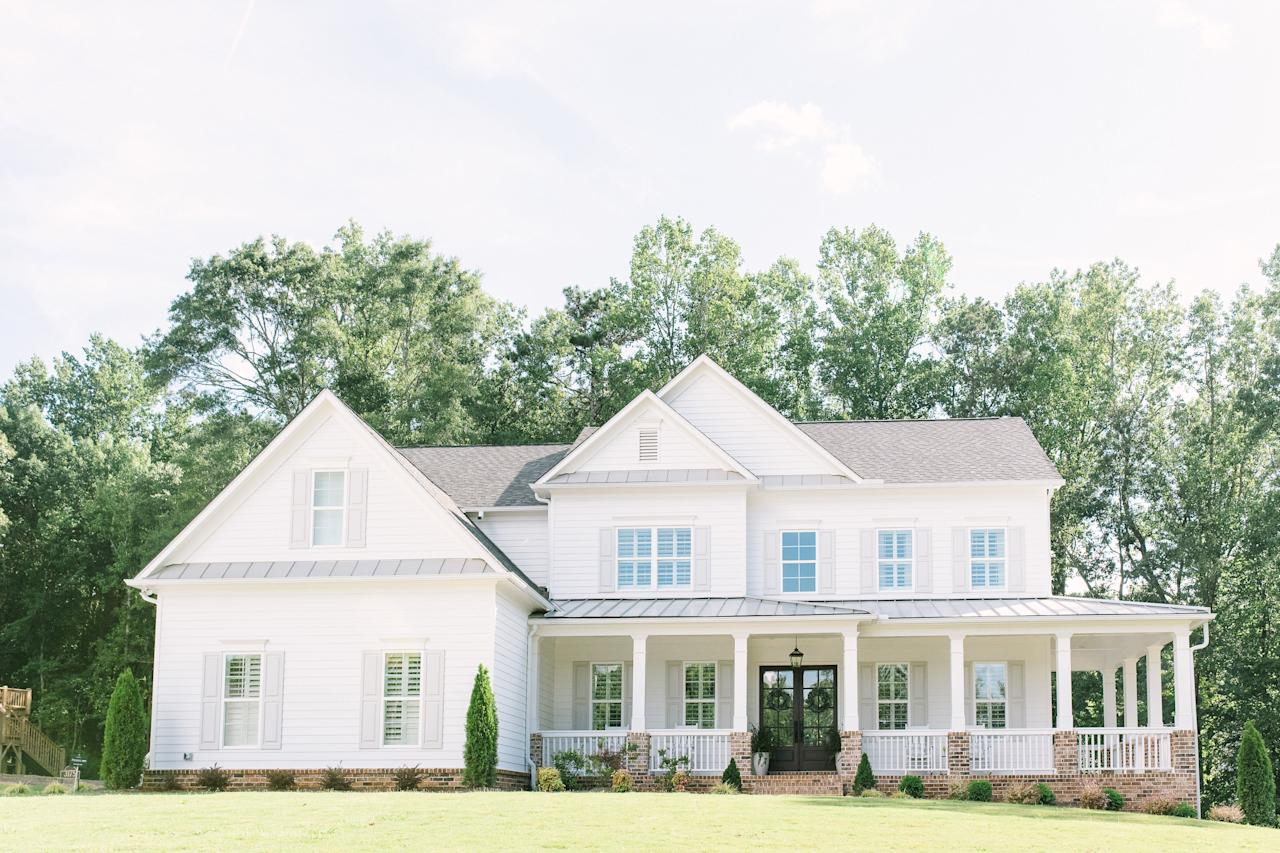 """<p>Casey Rutherford of <a href=""""https://www.betweenwhitehouses.com"""">Between White Houses</a> used the off-white shade <a href=""""https://www.ppgpaints.com/color/color-families/neutrals/gypsum"""">Gypsum</a> from PPG for the siding color and <a href=""""https://www.ppgpaints.com/color/color-families/neutrals/swirling-smoke"""">PPG's Swirling Smoke</a> for the shutters of her Georgia farmhouse to create a quintessential natural color palette. </p>"""