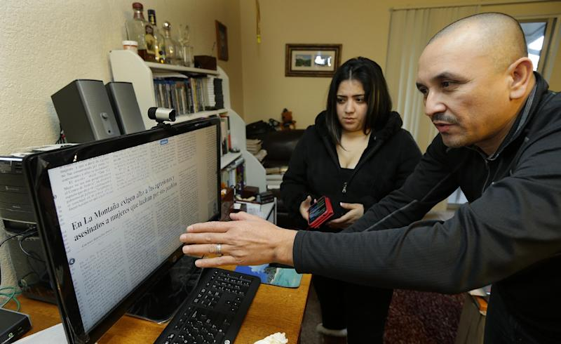 Grisel Rodriguez, second from left, and Jose Avila, right, look at an online newspaper, Tuesday, Nov. 26, 2013, in their apartment in Renton, Wash. The paper had a story about Avila's wife, Nestora Salgado, who has been detained since she was arrested Aug. 21, 2013 in the state of Guerrero, south of Mexico City, where she had been leading a vigilante group targeting police corruption and drug cartel violence. Rodriguez is Salgado's daughter. (AP Photo/Ted S. Warren)