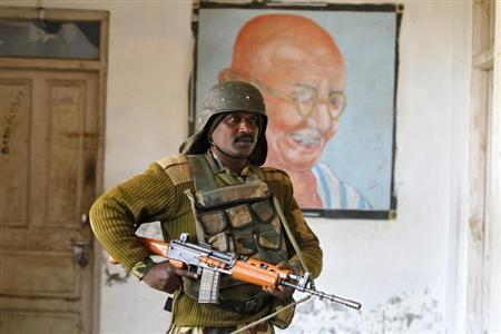 An Indian security personnel stands guard in front of a portrait of Mahatma Gandhi at a polling station in Merhama