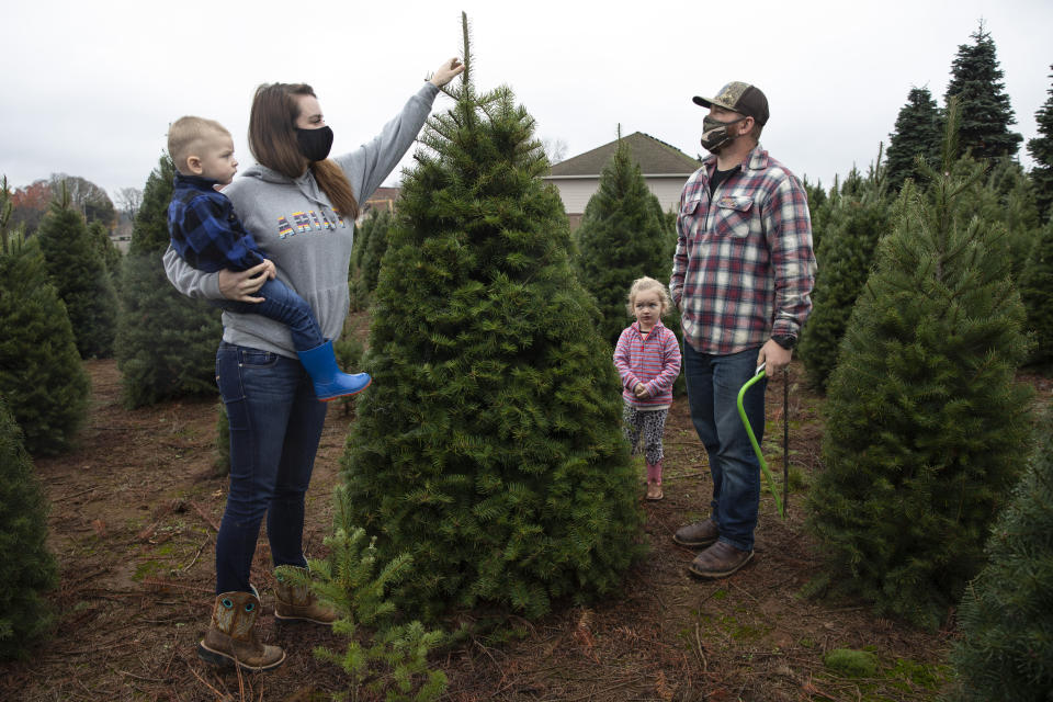 Josh and Jessica Ferrara shop for Christmas trees with son Jayce, 1 year and Jade, 3 years, at Sunnyview Christmas Tree farm on Saturday, Nov. 21, 2020 in Salem, Ore. It's early in the season, but both wholesale tree farmers and small cut-your-own lots are reporting strong demand, with many opening well before Thanksgiving. (AP Photo/Paula Bronstein)