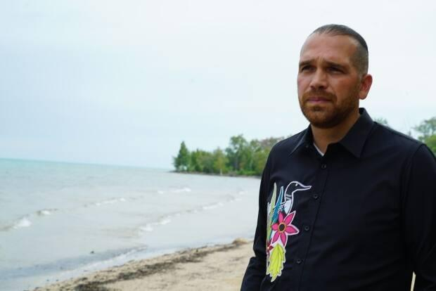Kettle and Stony Point First Nation Chief Jason Henry stands on the beach, with Stony Point in the background, in a file photo. (Kate Dubinski/CBC - image credit)