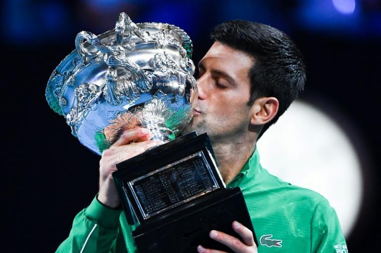 World number one Novak Djokovic kisses the Australian Open trophy following his victory against Austria's Dominic Thiem in the 2020 final. This year the top stars face the threat of sanctions if they breach stringent Covid-19 protocols