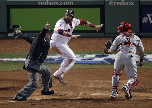 Boston Red Sox's Jonny Gomes, middle, reacts after sliding safely past St. Louis Cardinals catcher Yadier Molina during the third inning of Game 6 of baseball's World Series Wednesday, Oct. 30, 2013, in Boston. Gomes scored from first on a double by Shane Victorino. (AP Photo/Charlie Riedel)