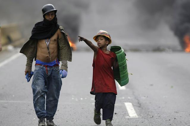 <p>A demonstrator and boy wearing a helmet and holding a shield, walk on a blocked highway as a barricade burns in the background, during a national sit-in against President Nicolas Maduro, in Caracas, Venezuela, Monday, May 15, 2017. (AP Photo/Fernando Llano) </p>