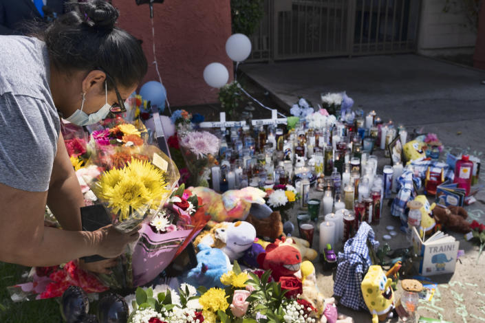 A woman leaves flowers at a memorial for three children who were killed at the Royal Villa apartments complex in the Reseda section of Los Angeles, on Monday, April 12, 2021. Authorities have identified 3-year-old Joanna Denton Carrillo, her 2-year-old brother, Terry, and 6-month-old sister, Sierra, as the three young children who were killed over the weekend. Their mother is the suspect in their deaths and was being held in a central California jail. (AP Photo/Richard Vogel)
