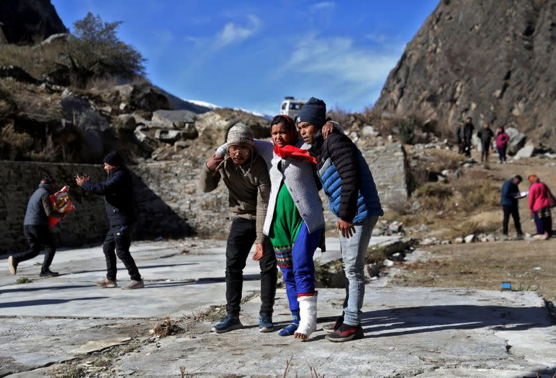 People help an injured woman to board a helicopter after a flash flood swept a mountain valley destroying dams and bridges, at Lata village