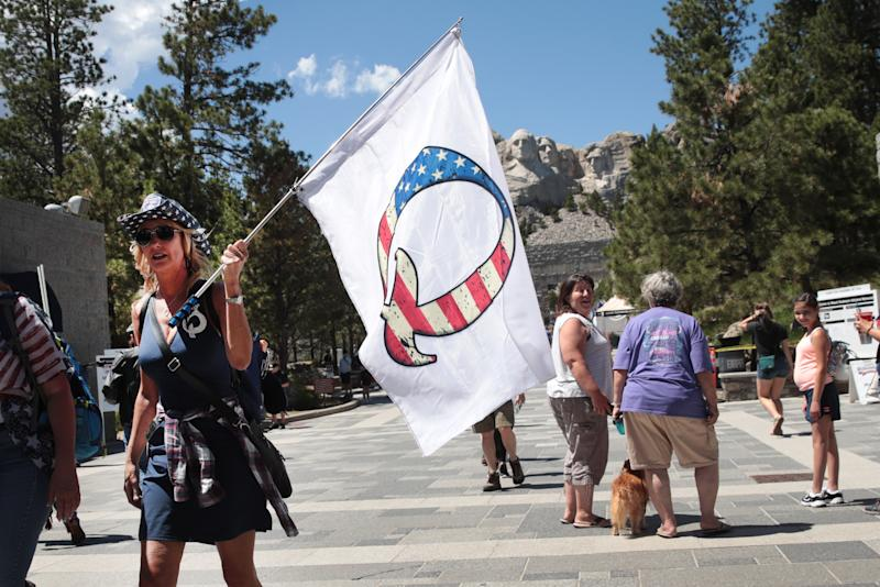 KEYSTONE, SOUTH DAKOTA - JULY 01: A Donald Trump supporter holding a QAnon flag visits Mount Rushmore National Monument on July 01, 2020 in Keystone, South Dakota. President Donald Trump is expected to visit the monument and make remarks before the start of a fireworks display on July 3. (Photo by Scott Olson/Getty Images)