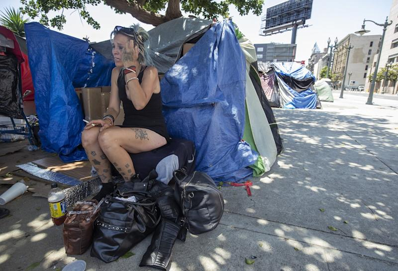Tasha Tinsley, 41, sits next to a friend's tent at an encampment near 3rd and Main streets in downtown Los Angeles.
