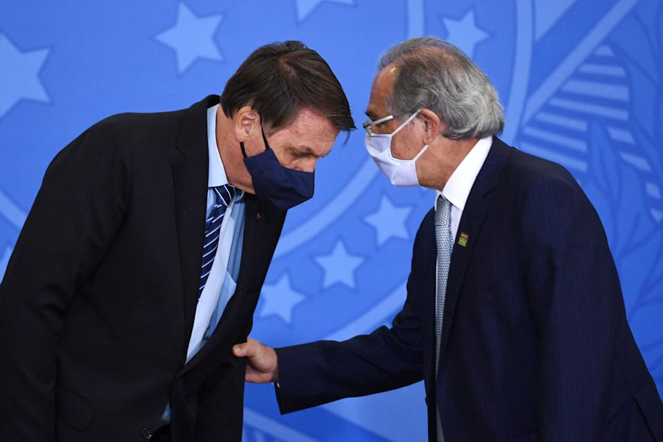 Brazilian President Jair Bolsonaro (L) and his Finance Minister Paulo Guedes talk during the signing ceremony of the Provisional Measure to improve the business environment in Brazil, at Planalto Palace in Brasilia, on March 29, 2021. - Bolsonaro faces a severe crisis between his foreign Minister Ernesto Araujo and the National Congress where he is the target of criticism for the way he has conducted the Brazilian foreign policy. (Photo by EVARISTO SA / AFP) (Photo by EVARISTO SA/AFP via Getty Images)