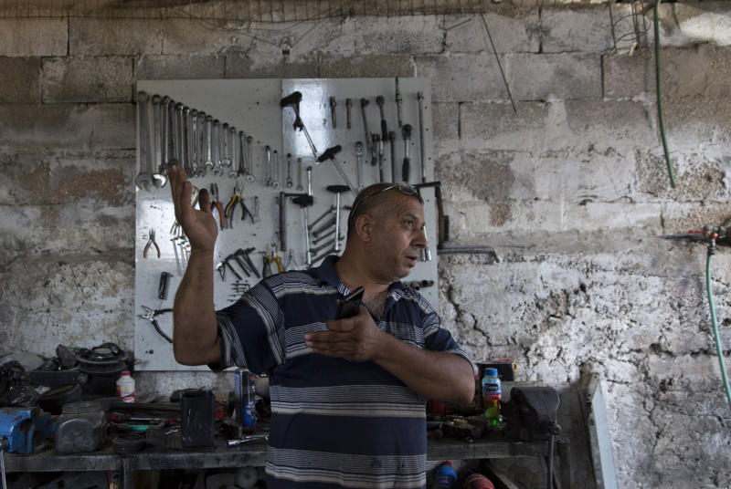 In this Wednesday, Sept. 11, 2019 photo, Palestinian Barhoum Saleh gives an interview at his roadside mechanic shop, near the West Bank Israeli settlement of Elkana, west of Qalqiliya. Saleh is among the 2.5 million Palestinians in the West Bank who have no voice in choosing Israel's next government and no control over whether it decides to annex part or all of the occupied territory, as Prime Minister Benjamin Netanyahu has vowed to do. (AP Photo/Nasser Nasser)