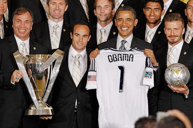 "WASHINGTON, DC - MAY 15: U.S. President Barack Obama (2nd R) poses for photographs with the Major League Soccer champions Los Angeles Galaxy, including General Manager and Head Coach Bruce Arena (L) and mid-fielders Landon Donovan and David Beckham (R) in the East Room of the White House May 15, 2012 in Washington, DC. Players from the Galaxy also participated in a ""Let's Move!"" question and answer session with school-age sports fans and first lady Michelle Obama after the ceremony. (Photo by Chip Somodevilla/Getty Images)"