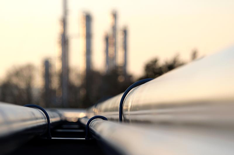 Pipelines headed towards a refinery in the background.