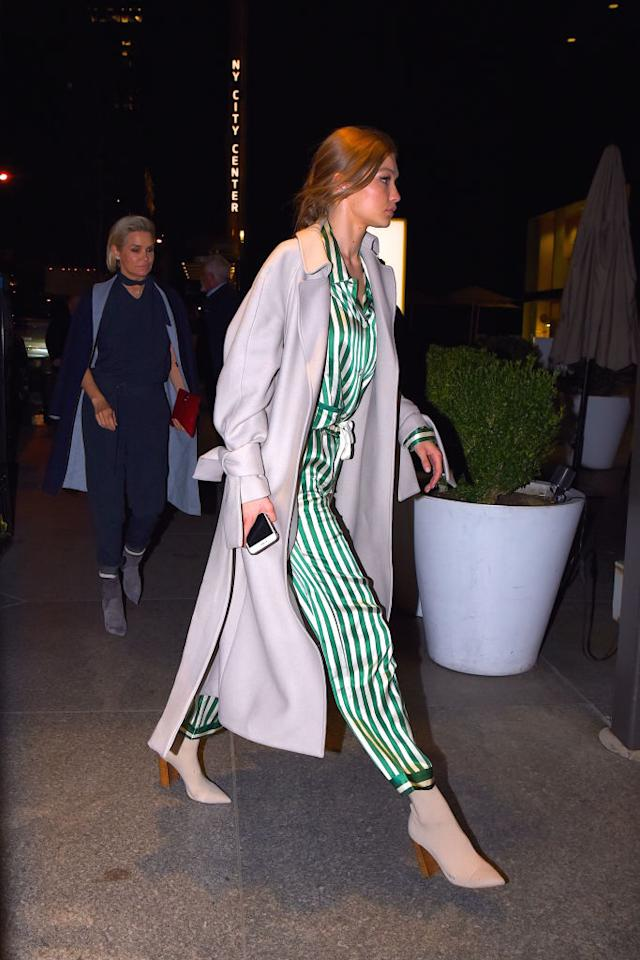 <p>From day 'til dark, the model opted to stay in her Pjs for dinner with mom, switching her stilettoes for Tony Bianco ankle boots and topping the outfit with a long grey coat. <i>(Photo via Getty) </i></p>