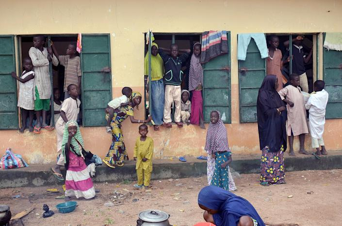 A picture taken on August 21, 2014 shows Internally Displaced People standing outside a classroom at Gulak camp in Nigeria's northeastern Adamawa State (AFP Photo/Olatunji Omirin)