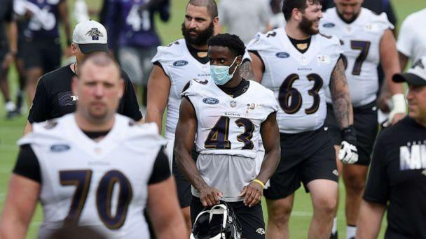 PHOTO: Baltimore Ravens running back Justice Hill wears a mask as walks off the field after an NFL football training camp practice, July 29, 2021, in Owings Mills, Md. (Gail Burton/AP)