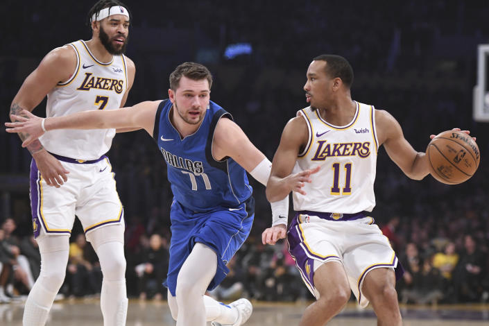 Dallas Mavericks guard Luka Doncic (77) defends Los Angeles Lakers guard Avery Bradley (11) during the first half of an NBA basketball game Sunday, Dec. 29, 2019, in Los Angeles. (AP Photo/Michael Owen Baker)