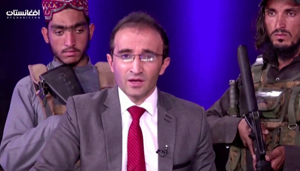 A TV news anchor is flanked by armed Taliban fighters. (Reuters)