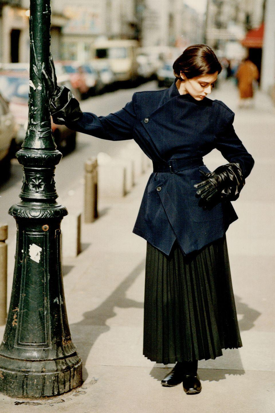 <p>A model wears a belted jacket and pleated skirt by Yohji Yamamoto.</p>