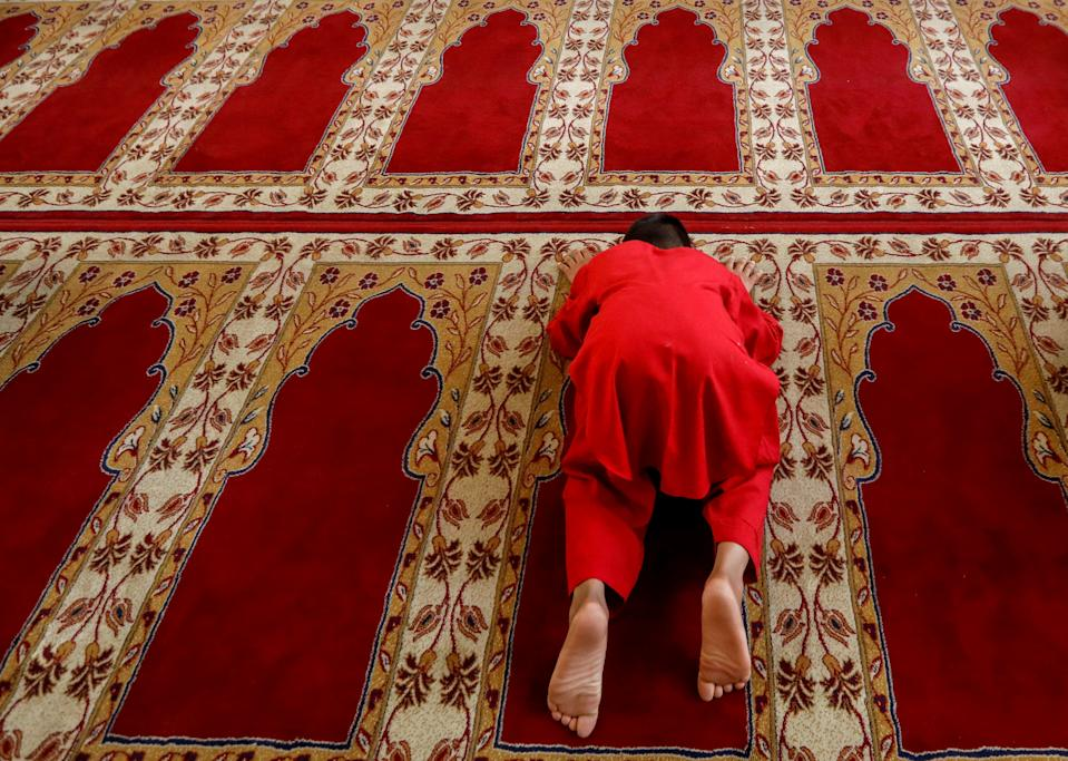 An Afghan boy prays during the Muslim festival of Eid al-Adha, amid the spread of the coronavirus disease (COVID-19), in Kabul, Afghanistan July 31, 2020. REUTERS/Mohammad Ismail TPX IMAGES OF THE DAY