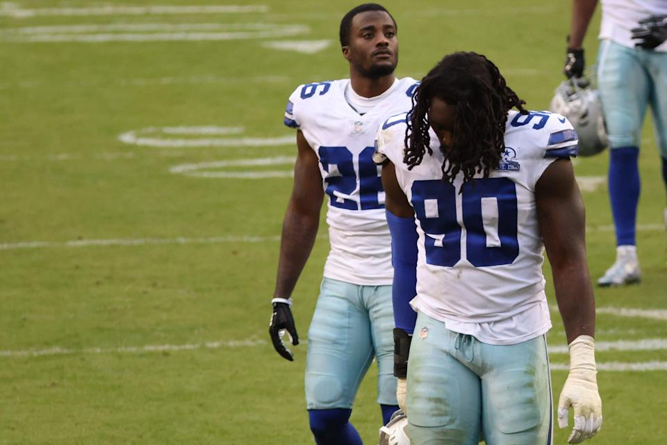 Dallas Cowboys defensive end Demarcus Lawrence (90) and Cowboys cornerback Jourdan Lewis (26) walk off the field after their game against the Washington Football Team at FedEx Field.