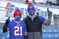 Buffalo Bills fans Scott Hammond, right, and his son Landon pose for a photograph as their team warms up before an NFL wild-card playoff football game against the Indianapolis Colts, Saturday, Jan. 9, 2021, in Orchard Park, N.Y. The Hammonds were among the lucky 6,700 few to land tickets for the Bills wild-card playoff against the Indianapolis Colts for Buffalo's first home playoff game in 24 years. (AP Photo/Jeffrey T. Barnes)