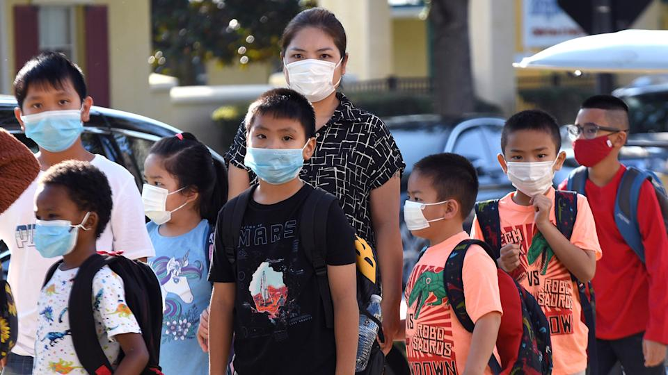 Students wearing face masks arrive on the first day of classes for the 2021-22 school year at Baldwin Park Elementary School in Orlando, Fla.