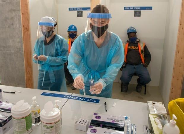 Nurses administer rapid COVID-19 tests at a construction site in Toronto on Thursday, Feb. 18, 2021.
