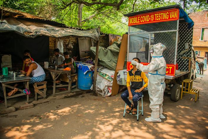 """A health worker taking a nasal swab from a man, close to a restaurant. The mobile Covid-19 testing van runs through slum areas conducting rapid antigen tests. <p class=""""copyright"""">Pradeep Gaur/SOPA Images/LightRocket via Getty Images</p>"""