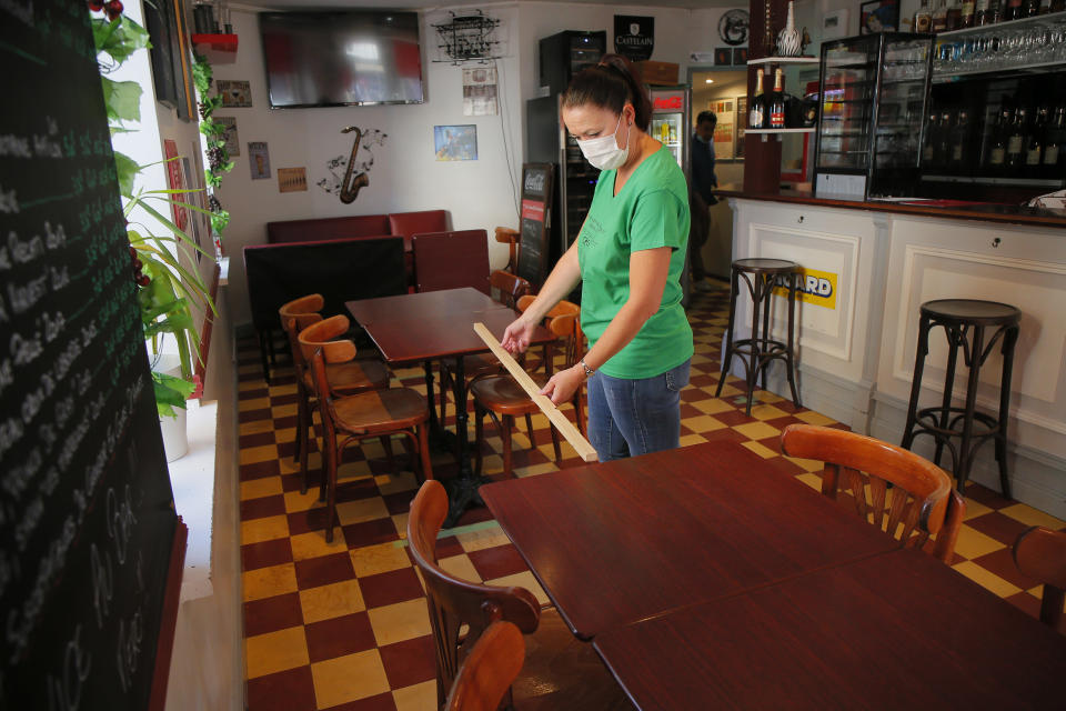 A woman measures the distance between table in a restaurant of Lille, northern France, Tuesday June 2, 2020. The French way of life resumes Tuesday with most virus-related restrictions easing as the country prepares for the summer holiday season amid the pandemic. Restaurants and cafes reopen Tuesday with a notable exception for the Paris region, the country's worst-affected by the virus, where many facilities will have to wait until June 22 to reopen. (AP Photo/Michel Spingler)
