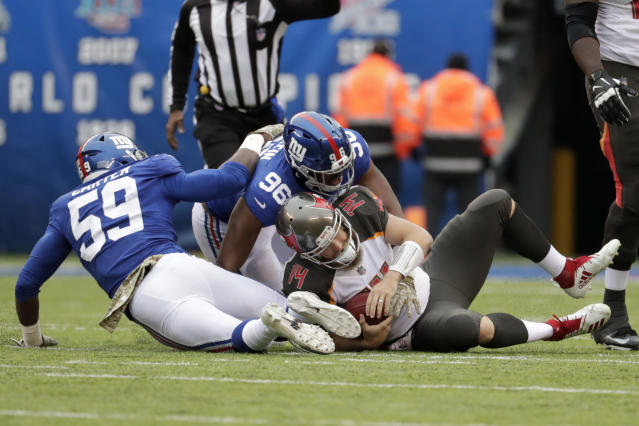 Tampa Bay Buccaneers quarterback Ryan Fitzpatrick, right, is sacked by New York Giants' Lorenzo Carter, left, and Kareem Martin during the first half of an NFL football game, Sunday, Nov. 18, 2018, in East Rutherford, N.J. (AP Photo/Julio Cortez)
