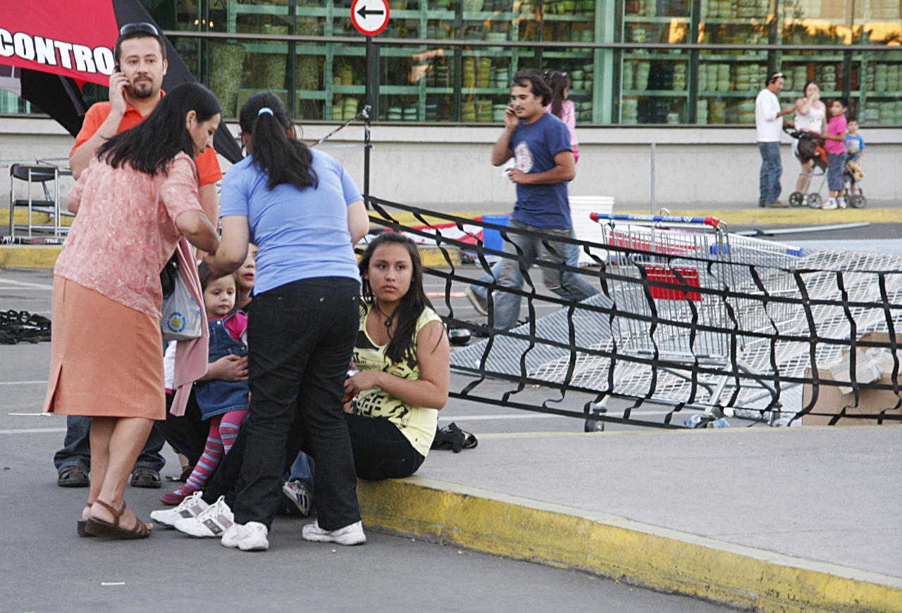 People gather outside a supermarket after an earthquake was felt in Talca, Chile, Sunday, March 25, 2012. A magnitude-7.2 earthquake has struck just off the coast of central Chile, prompting an emergency evacuation order for people living near the ocean in case it spawns a tsunami. (AP Photo/Fabian Suazo)