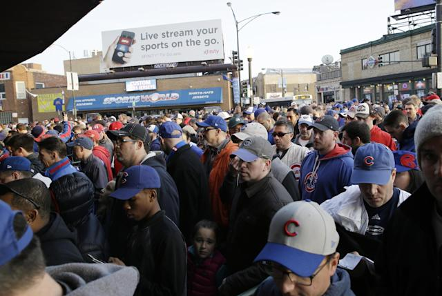 Baseball fans arrive at Wrigley Field before a Major League Baseball season-opening game between the Chicago Cubs and the St. Louis Cardinals in Chicago, Sunday, April 5, 2015. (AP Photo/Nam Y. Huh)