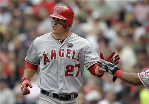 Los Angeles Angels player Mike Trout (27) is congratulated by a teammate after scoring on a single by Mark Trumbo during the fifth inning of a baseball game against the Boston Red Sox, Sunday, June 9, 2013, at Fenway Park in Boston. (AP Photo/Mary Schwalm)