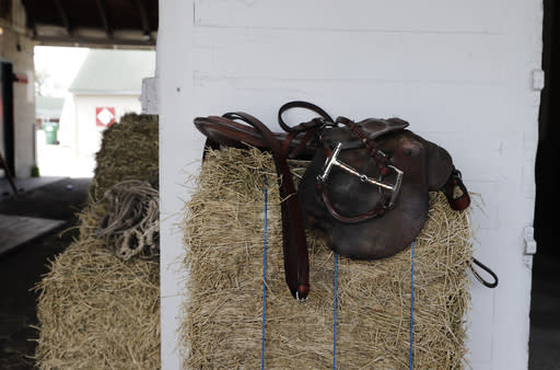 A jockey's saddle sits on a bail of hay at Churchill Downs, Wednesday, April 22, 2020, in Louisville, Ky. The Kentucky Derby has been postponed until Sept. 5, because of the coronavirus. (AP Photo/Darron Cummings)