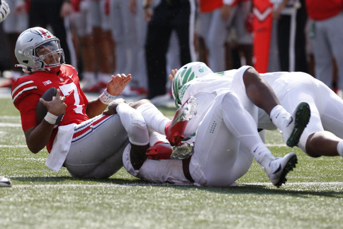 Ohio State quarterback C.J. Stroud, left, is sacked by Oregon defensive end DJ Johnson, center, and defensive lineman Brandon Dorlus on the final play of the game in the second half of an NCAA college football game Saturday, Sept. 11, 2021, in Columbus, Ohio. Oregon beat Ohio State 35-28. (AP Photo/Jay LaPrete)