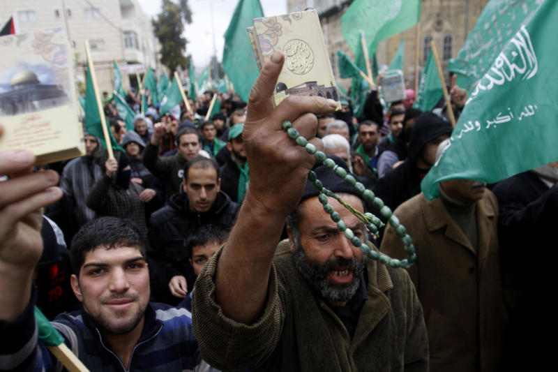 Hamas supporters wave the movement's flags and hold up Qurans during a pro-Hamas rally in the West Bank city of Hebron, Friday , Nov 23, 2012. (AP Photo/Nasser Shiyoukhi)