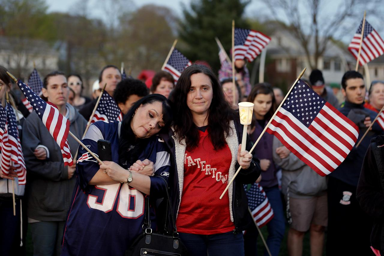 People gather on a field during a vigil for the victims of the Boston Marathon bombing, Saturday, April 20, 2013, in Watertown, Mass. Suspected bomber Dzhokhar Tsarnaev is hospitalized in serious condition with unspecified injuries after he was captured in an all day manhunt the day before. (AP Photo/Julio Cortez)