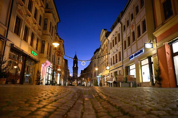 18 December 2020, Saxony, Bautzen: Christmas lights hang over the empty Reichenstraße in front of the Reichenturm. So far, there has been no sign of a turnaround in new infections in the state of Saxony. According to the Ministry of Health in Dresden, the seven-day incidence climbed to 415 on Thursday (17.12.2020). On Wednesday, the value was still at 407. Saxony thus continues to be well ahead of all other federal states. Photo: Sebastian Kahnert/dpa-Zentralbild/dpa (Photo by Sebastian Kahnert/picture alliance via Getty Images)