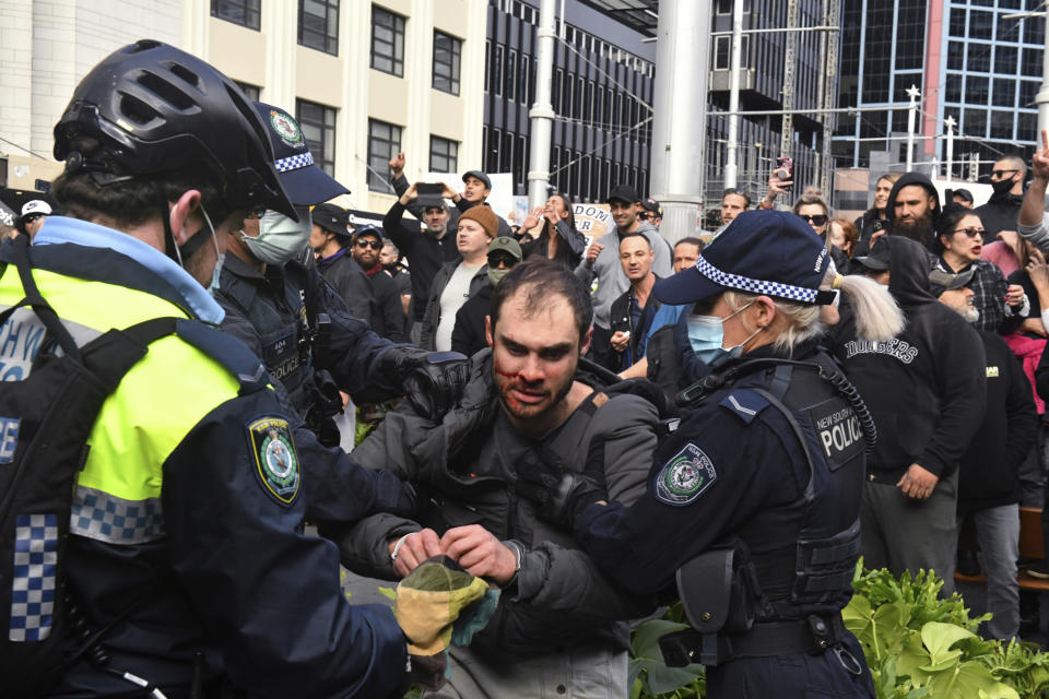 A protester, center, is arrested by police at a demonstration at Sydney Town Hall during a 'World Wide Rally For Freedom' anti-lockdown rally in Sydney, Saturday, July 24, 2021. (Mick Tsikas/AAP Image via AP)
