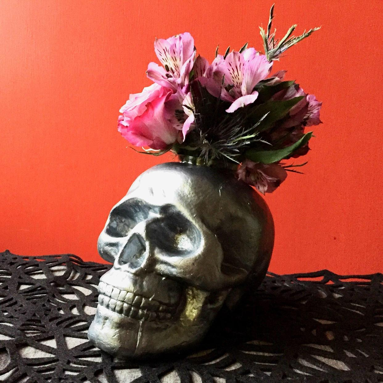 Decoration idea Halloween black skull serving as a vase with pink flowers